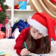 Beautiful little girl writes letter to Santa Claus in festively decorated room — Stock Photo #16839657