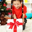 Little girl with present box near christmas tree — Stockfoto