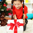 Little girl with present box near christmas tree — Stock Photo