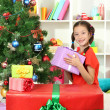 Little girl with large gift box near christmas tree — Stock Photo #16839745