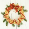 Christmas wreath of dried lemons with fir tree and bow, on white wooden background — 图库照片