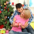 Young happy couple with presents sitting near Christmas tree at home — Stock Photo #16839965