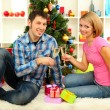 Young happy couple holding glasses with champagne near Christmas tree at home — Stock Photo #16839969