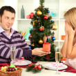 Young happy couple with presents sitting at table near Christmas tree — Stock Photo #16839977