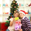 Young happy couple with presents sitting near Christmas tree at home — Stock Photo #16839993