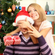 Young happy couple with presents sitting near Christmas tree at home — Stock Photo #16839999