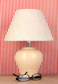 Table lamp and glasses on striped background — Stock Photo