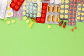 Capsules and pills packed in blisters on green background — Stock Photo