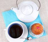 Top view of cup of tea and teapot on tablecloths — Stockfoto