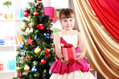Beautiful little girl in holiday dress with gift in their hands in festively decorated room — Stock Photo