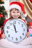 Beautiful little girl with clock in anticipation of New Year in festively decorated room — Foto de Stock