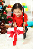 Little girl with present box near christmas tree — Foto Stock