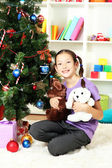 Little girl holding toys near christmas tree — Stok fotoğraf