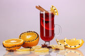 Fragrant mulled wine in glass with spices and oranges around on purple background — Stock Photo