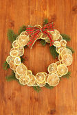 Christmas wreath of dried lemons with fir tree and bow, on wooden background — Stock Photo