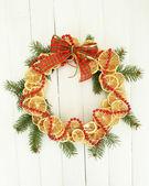 De kroon van kerstmis van gedroogde citroenen met fir tree en boog, op witte houten achtergrond — Stockfoto