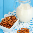 Tasty pretzels in white bowl and milk jug on wooden table close-up — Stock Photo #16840147