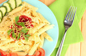 Rigatoni pasta dish with tomato sauce on wooden table close up — Stock Photo