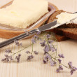 Butter on wooden holder and bread on wooden table close-up — Stock Photo #16864965