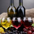 Bottles and glasses of wine and grapes on grey background — Stock Photo #16865411