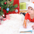 Little boy in Santa hat writes letter to Santa Claus — Stock Photo #16865909
