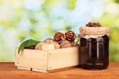 Jam-jar of walnuts and wooden box on green background — Stock Photo