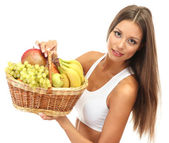 Beautiful young woman with fruits in basket, isolated on white — Stock Photo