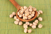 White chickpeas over wooden spoon on color background — Stock Photo