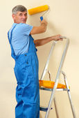 Male painter paints wall in room close-up — Stock Photo