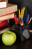 Books and magister cap against school board on wooden table close-up — Stock Photo