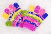 Children's mittens in snow — Stock Photo