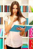 Young attractive female student reads book in library — Stock Photo
