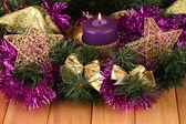 Composição de Natal com velas e decorações em cores púrpura e ouro sobre fundo de madeira — Fotografia Stock