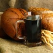 Tankard of kvass and rye breads with ears, on burlap background — Stock Photo #16872379