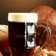 Tankard of kvass and rye breads with ears, on wooden table on brown background — Stock Photo #16872389