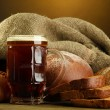 Tankard of kvass and rye breads with ears, on wooden table on brown background — Stock Photo #16872391