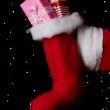 Santa Claus hand holding gifts on bright background — Stock Photo