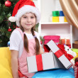 A little girl opens a gift in festively decorated room — Stock Photo #16873267