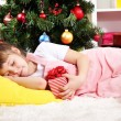 The little girl fell asleep with gift in their hands in festively decorated room — Stock Photo #16873277