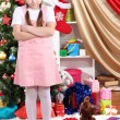 Upset by little girl near the Christmas tree in festively decorated room — Stockfoto