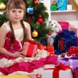Beautiful little girl in holiday dress with gift in their hands in festively decorated room — Stock Photo #16873291
