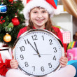 Beautiful little girl with clock in anticipation of New Year in festively decorated room — Stok Fotoğraf #16873297