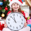 Foto de Stock  : Beautiful little girl with clock in anticipation of New Year in festively decorated room