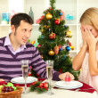 Young happy couple with presents sitting at table near Christmas tree — Stock Photo