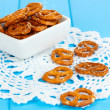 Tasty pretzels in white bowl on wooden table close-up — Stock Photo #16873481