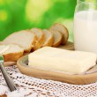 Butter on wooden holder surrounded by bread and milk on natural background — Stock Photo #16874059