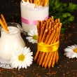 Tasty crispy sticks with pitcher and glass with sour cream on wooden table close-up — Stock Photo #16874241