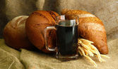 Tankard of kvass and rye breads with ears, on burlap background — Стоковое фото