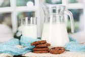 Pitcher and glass of milk with cookies on crewnecks knitwear on wooden table on window background — Stock Photo