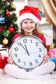 Beautiful little girl with clock in anticipation of New Year in festively decorated room — Zdjęcie stockowe